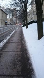 歩道の雪2日目 (その3): 大学の建物が続く道路。大学院まであと10分強。大学区域に入ると歩道がすっかり除雪されています。